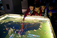 """24 April 2004 - Caen, France - Schoolchildren from Seneffe in Belgium examine a map of the D-Day Overlord operations on display at the Memorial museum in Caen, France, 24 April 2004. The school trip to the museum and then to the D-Day sites is part of a """"Democracy Year"""" organized by the teachers."""