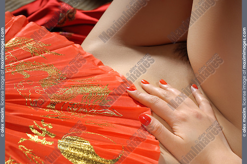 Closeup of a beautiful naked asian woman body covered with a red fan