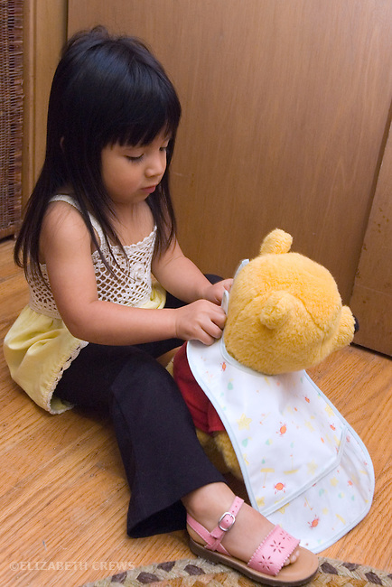 Berkeley CA Girl, age two and a half, Guatemalan, getting Pooh ready for lunch with bib  MR