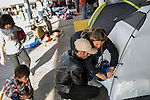 An Afghan couple prepare to leave with their two children. They have traveled a month and want to settle in Sweden. <br /> <br /> Hundreds of refugees from mostly Syria and Afghanistan gather at the Budapest Keleti railway station waiting for trains to leave for destinations such as Austria, Germany and Sweden, in Budapest, Hungary, on Tuesday, Sept. 8, 2015. Hungary's Prime Minister Viktor Orban created an anti-refugee campaign to generate hate against those fleeing war in their home countries. The country is currently 50% xenophobic and the government has become increasingly authoritarian.