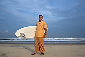 "Gaura Gopala, a devotee of the Kaliya Mardana Krishna Ashram poses for a portrait at the beach before he heads out for a surf on Arabian Sea in Mangalore beach, Karnataka, India.  ..Krishna devotees in the Gaudiya Vaishnava tradition of Hinduism, they are known collectively as the ""surfing swamis."" The ""surfing ashram"" is growing in popularity and surfing here is a form of meditation, a spiritual practice leading to heightened states of awareness."
