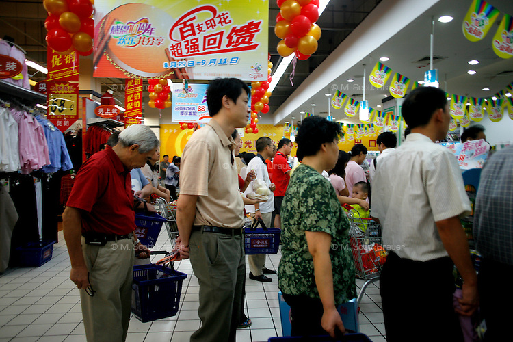 People wait in line for a cashier at the RT Mart supermarket in Nanjing, China.