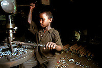 Faruq, who is around seven or eight years old, making rickshaw components in a factory workshop. Faruq starts work at 8 o' clock in the morning and finishes at 7 o' clock in the evening.