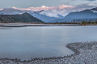 Full moon rising over Southern Alps with Mount Tasman and Mount Cook and reflections in Cook River in foreground, Westland National Park, World Heritage Area, West Coast, New Zealand