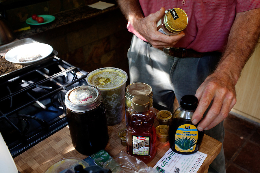 "Laguna Beach, California, October, 26, 2010 - Bill Roley pulls out a host of sweetners - honey, agave nectar, maple syrup, and home made maple butter - that he has blended with cannabis distilled by cooking it with vegetable glycerin. Roley, who suffers from a lack of appetite due to extensive radiation from throat cancer, has been looking for alternatives to smoking medical marijuana for those who like himself have trouble because of his condition or who just don't like to smoke. Roley is a member of the Laguna Woods for Medical Cannabis, a collective of about 100 members that operates as a dispensary for medical marijuana in the nearby senior community of Laguna Woods Village. Up until this month, the members were allowed to grow marijuana within their own gardens. Collective Chairman, Lonnie Painter says, ""We do this by the book, to the letter of the law. We are not potheads. We are people with legitimate medical needs."" Despite their best efforts, the group has faced some challenges recently. The board that oversees the community recently banned the growing of marijuana in the community gardens, despite the fact that each person has their own fenced and locked garden and the entire compound is surrounded by a chain-linked fence with barbed-wire. California's Compassionate Use Act, passed in 1996, allows people with a prescription to use and cultivate medicinal marijuana....."