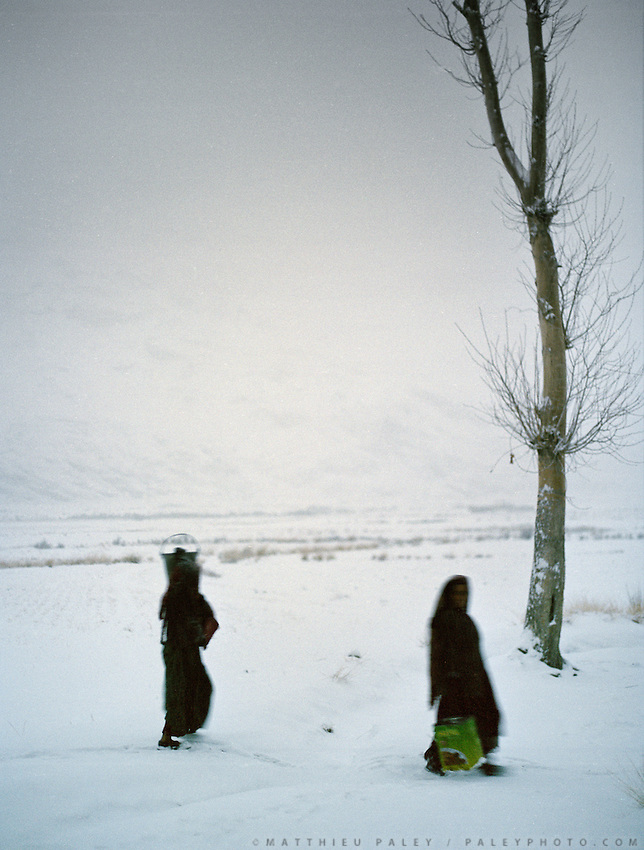 At dusk, women coming back home carrying water. .Winter expedition through the Wakhan Corridor and into the Afghan Pamir mountains, to document the life of the Afghan Kyrgyz tribe. January/February 2008. Afghanistan