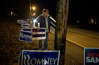A Rick Santorum supporter places campaign signs outside the site of the GOP debate at St. Anselm College in Manchester, New Hampshire, on Jan. 7, 2012. Santorum is seeking the 2012 Republican presidential nomination.