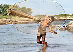 A boy throws a fishing net in a river near Santa Paula, a hot and isolated village in northwestern Nicaragua.