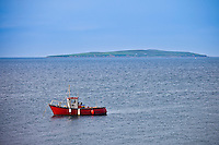 Fishing boat with Saltee Islands in background, Irish Sea at Kilmore, County Wexford, Ireland