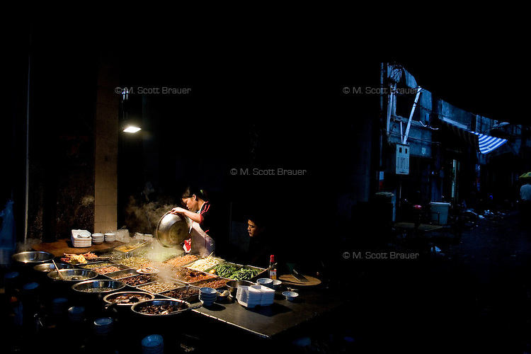 The cook at an alley restaurant begins work for the evening in Haikou, China.