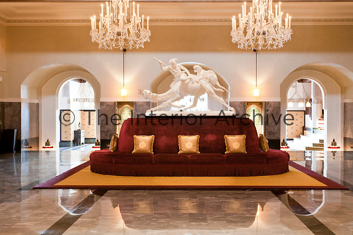 A life-size sculpture displayed on a round sofa in the lobby