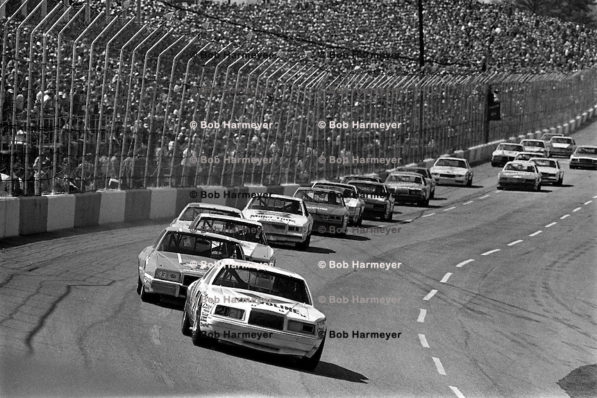 HAMPTON, GA - MARCH 27: Buddy Baker in the Wood Brothers Ford is followed by Richard Petty in the Petty Enterprises Pontiac and the rest of the field in the Coca-Cola 500 NASCAR Winston Cup race at Atlanta Motor Speedway near Hampton, Georgia, on March 27, 1983.