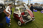 Floral Park, New York, U.S. - April 27, 2014 - A family with young children look at the 1958 BMW Isetta 300 at the 35th Annual Antique Auto Show at Queens Farm. Designed by the Italian refrigerator company ISO, it has a refrigerator-like front door which swings open to let the driver and passenger enter.