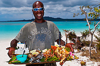 A Kanak (Melanesian) man serving a seafood lunch that he has just cooked on Brush Island, New Caledonia Barrier Reef off Ile des Pins (Isle of Pines), New Caledonia