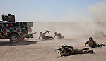 17th Iraqi Division soldiers jump to combat positions from a moving truck during training exercises August 30, 2010 at the Joint Security Station (JSS) Deason in Mahmoudiyah, Iraq.