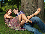 Young man tickling laughing young laughing woman's bare feet in the nature. Focus on feet.