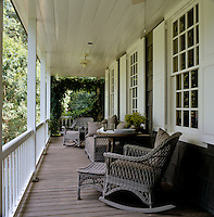 Wicker rocking chairs and a large wicker sofa furnish the  the wisteria-clad veranda of this shingled house