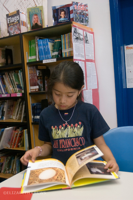 Oakland CA 2nd grade student looking over books at school library