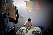 A Chinese worker eats his breakfast in his dormitory at the Chinese Colony in the Adani Power plant in Mundra port industrial city of Gujarat, India. Indian power companies have handed out dozens of major contracts to Chinese firms since 2008. Adani Power Ltd have built elaborate Chinatowns to accommodate Chinese workers, complete with Chinese chefs, ping pong tables and Chinese television. Chinese companies now supply equipment for about 25% of the 80,000 megawatts in new capacity.