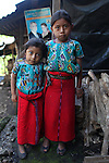 María (left) and her sister Margarita, Ixil Mayan girls from the town of Juá, stand outside their home. In the background, a poster of Guatemalan President Otto Pérez Molina's Partido Patriota, or Patriot Party (PP), adorns a wall. Otto Pérez Molina, a former general during the Internal Armed Conflict (1960-1996) in the Ixil region that includes Chajul, is accused of carrying out atrocities against the local Ixil Mayan population. The town of Juá sits a few hundred meters from the controversial Xacbal hydroelectric dam, a Honduran venture ran by Fredy Nasser's Grupo Terra. San Gaspar Chajul, Quiché, Guatemala. August 2012.