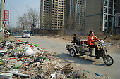 People drive past garbage left outside a building site in Hebei, on the outskirts of Beijing, where rural land is increasingly destroyed to make way for urbanisation. <br /> <br /> China is pushing ahead with a dramatic, history-making plan to move 100 million rural residents into towns and cities over six years &mdash; but without a clear idea of how to pay for the gargantuan undertaking or whether the farmers involved want to move.<br />
