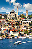 The Suleymaniye Mosque (Süleymaniye Camii, 1550-1558)  on the Third Hill and a ferry boat and the banks of the Golden Horn, Istanbul Turkey.