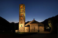 Low angle view of Sant Climent de Taull church, 1123, consecrated by Ramon Guillem, the bishop of Roda, Taull, Province of Lleida, Catalonia, Spain. The church of Sant Climent is the largest; its characteristic Lombard architecture and interior decoration make it the symbol of Catalan Romanesque architecture. Its most imposing feature is its bell tower: it is square in plan and soars from a simulated solid base to six storeys. This is a church with three naves separated by cylindrical columns, topped by three semicircular apses. It is known for its campanile and for its murals, which were removed to the MNAC (National Art Museum of Catalonia, Barcelona) in 1922, to prevent the theft of the murals. The Catalan Romanesque churches of the Vall de Boí were declared a World Heritage Site by UNESCO in November 2000. Picture by Manuel Cohen.