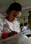 A Pakistani girl studying in a school for poor children held in St. Mathew's Church in the Punjab village of Bajasinsingh. This school is sponsored by the Church of Pakistan.  The teacher in the background is Nazia Shamim.