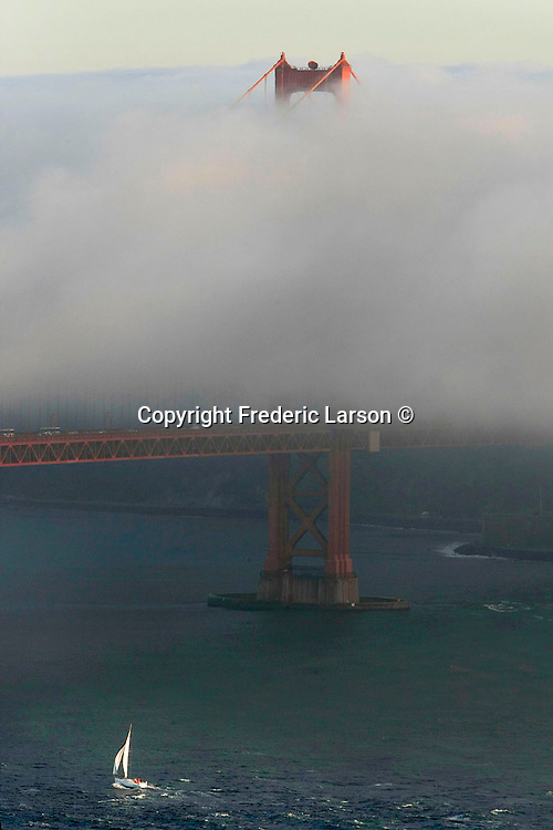Th San Francisco fog creeps over the deck of the Golden Gate Bridge as a cruise ship sails out at dusk in San Francisco California.