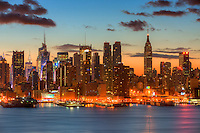 The Manhattan skyline during morning twilight as viewed over the Hudson River looking east from New Jersey.  The eastern sky and clouds were accented with tinges of orange that began to show in the hour before sunrise.