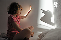 Girl in bed, playing with her shadow on wall (Licence this image exclusively with Getty: http://www.gettyimages.com/detail/90592926 )
