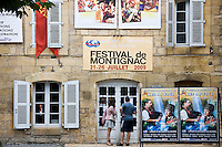 Visitors reading festival posters in the traditional town of Montignac, Dordogne region of France
