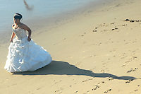 A woman in a wedding dress poses for photos at Santa Monica beach on Thursday, December 9, 2010.