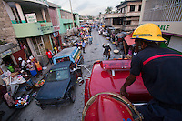 Firefighters atop a water truck in Port-au-Prince, Haiti try to head to an apartment fire. Heavy traffic and narrow streets prevented the crew from getting access to a blaze at a two-story home, so the owners had to put it out themselves with water buckets. A few dozen under-equipped firefighters are tasked with providing fire service to a damaged city of over two million people.