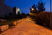 Night view, facing in the direction of Mount Zion, of a walking path just outside of the walls of the Old City of Jerusalem.