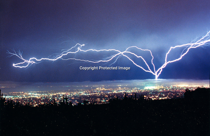 Bolt of Lightning strikes over the Oakland-San Francisco Bay Area. The lights of downtown Oakland in the forground. The storm lasted several hours on September 9, 1999. (photo copyright 1999 Ron Riesterer)