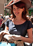 A woman in the Easter Parade in New York City wearing a large hat, white gloves, and pearls