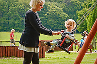 Young boy on a day out with his family, being pushed on a swing by his Mum.