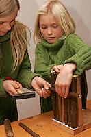 Kinder bauen Vogel-Nistkasten für Meisen, Vogelnistkasten, Nistkasten, Kinder nageln Holzstab als Verstrebung an Seitenteil