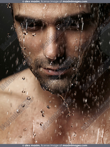 Thoughtful man face with his eyes down wet from shower water pouring on it, dramatic emotional portrait.
