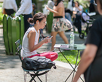 A visitor to Bryant Park in New York enjoys the 70 degree warm weather and the free wi-fi  on Thursday, May 12, 2016. While the warm weather continues the next couple of days may see showers. (© Richard B. Levine)