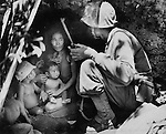 A member of a Marine patrol on Saipan finds a Japanese family hiding in a hillside cave. The mother, four children and doog took shelter from the fierce fighting. All civilian prisoners, consisting of Japanese, Koreans and Chamorros were removed to the safety of the beach area.