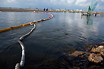 Oil booms are seen near the shoreline on June 24, 2010 where B.P. oil spill has reached land in Grand Isle, LA.