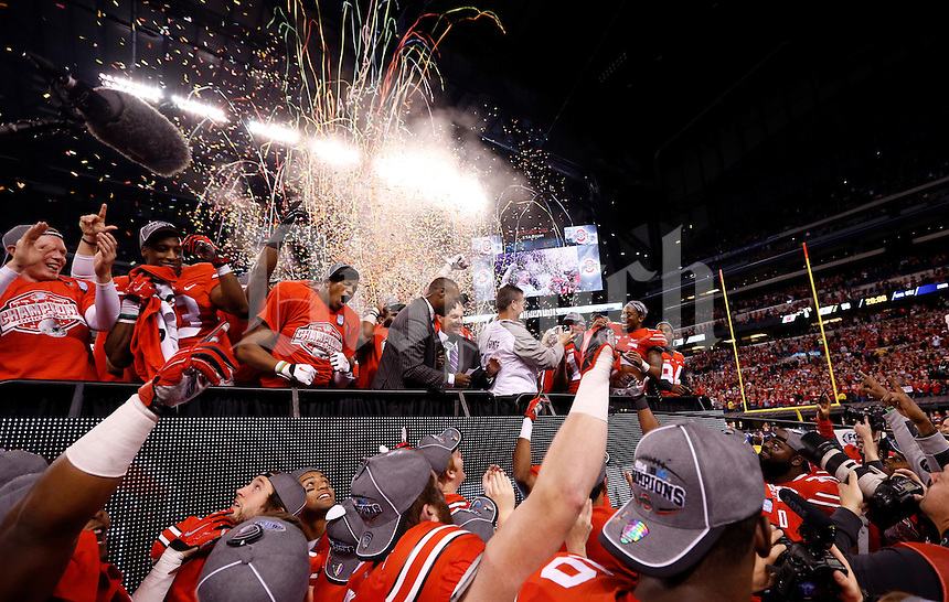 Ohio State players celebrate with the trophy following their 59-0 win over the Wisconsin Badgers in the Big Ten Championship game at Lucas Oil Stadium in Indianapolis on Dec. 6, 2014. (Adam Cairns / The Columbus Dispatch)