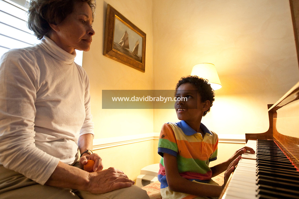 Marilyn Berger (L), widow of Don Hewitt, looks on as Danny Hodes, the 8 year-old Ethiopian boy she has taken in, plays the piano in her apartment in New York, NY, USA, 9 April 2010. Ms Berger met him in Addis Ababa while reporting there and helped him get surgery.