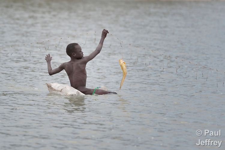 Duot Kuol, 13, catches fish in Poktap, a town in South Sudan's Jonglei State where conflict, drought and inflation have caused severe food insecurity. The Lutheran World Federation, a member of the ACT Alliance, is helping families tackle food problems, including by providing cash for the purchase of fishing line and hooks. This boy's family fled the region when war broke out in 2013, living as refugees in Uganda until returning in 2016.<br /> <br /> Parental consent obtained.