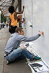 Jasper Goodall graphic  street artist making an art work New Goulston Street London E1. Just off Middlesex Street. Co-ordination by Jessica Tibbles in black dress from the Electric Blue Gallery.