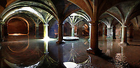 """Panoramic view of Manueline Cistern of the El Jadida (Mazagan) fortress, built by Francisco and Diogo de Arruda, 16th century, El Jadida, Morocco. El Jadida, previously known as Mazagan (Portuguese: Mazag""""o), was seized in 1502 by the Portuguese, and they controlled this city until 1769. The underground Cistern was originally designed to store munitions. It served as a fencing school before being used after completion of the town walls in 1541 as a tank to store water. The symmetrical construction has a vaulted roof supported by 25 circular and rectangular pillars, with just one central window in the ceiling, 3.5 m in diameter, producing a single shaft of light. The shallow sheet of water produces a shimmering reflection of the vaulted ceiling in the light. Picture by Manuel Cohen"""