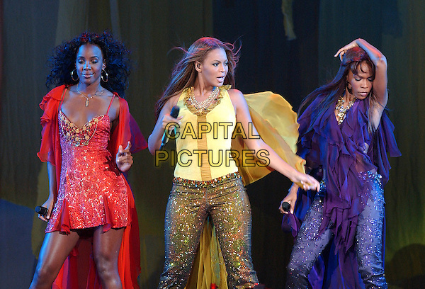 """KELLY ROWLAND, BEYONCE KNOWLES & MICHELLE WILLIAMS.Destiny's Child.""""Destiny Fulfilled ...And Lovin It"""" Tour.Mellon Arena.Pittsburgh, 20th July 2005.stage gig music half length half-length gold glitter trousers microphone yellow top red dress purple singing.www.capitalpictures.com.sales@capitalpictures.com.© Capital Pictures."""