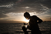 27 year old Maskuri (in cap) seen fishing with his friends on a small boat in the Java Sea in Tegal of Central Java region in Indonesia. Photo: Sanjit Das/Panos